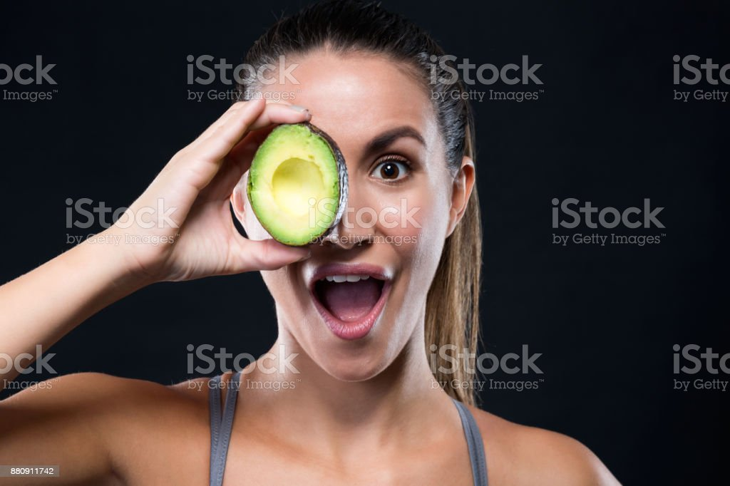 Beautiful young woman holding avocado over black background. stock photo