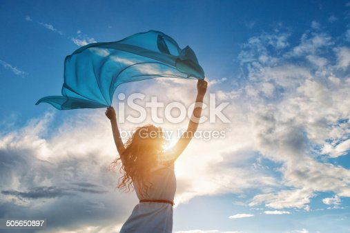 istock Beautiful young woman holding blue scarf on the wind 505650897
