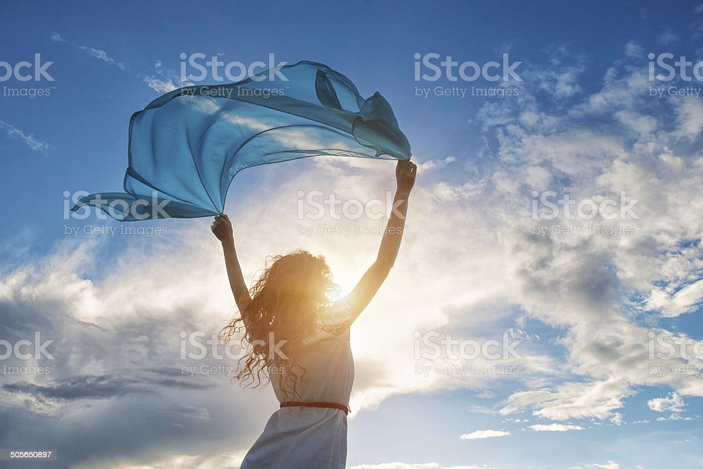 Beautiful young woman holding blue scarf on the wind stock photo