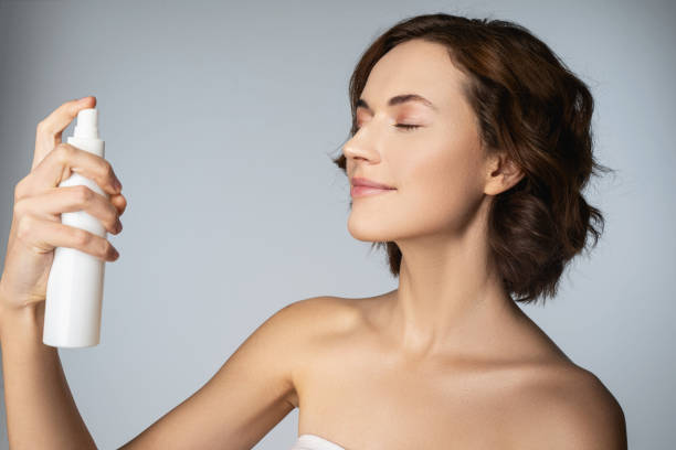 Beautiful young woman holding bottle of cosmetic spray stock photo