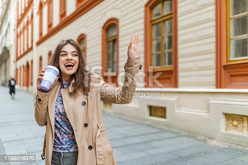531098549istockphoto Beautiful young woman holding coffee cup and smiling while walking along the street 1168016370