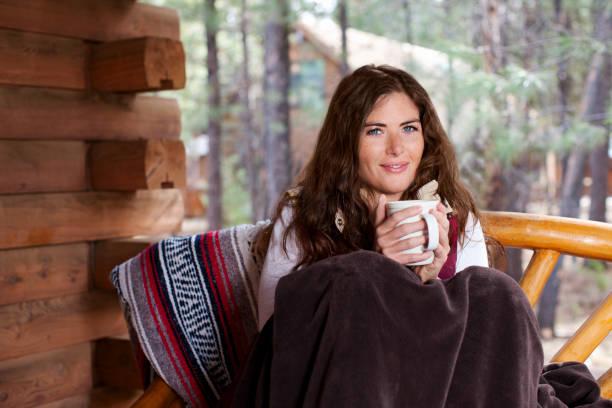 schöne junge frau holding kaffee tasse im winter-kabine, copyspace - veranda decke stock-fotos und bilder