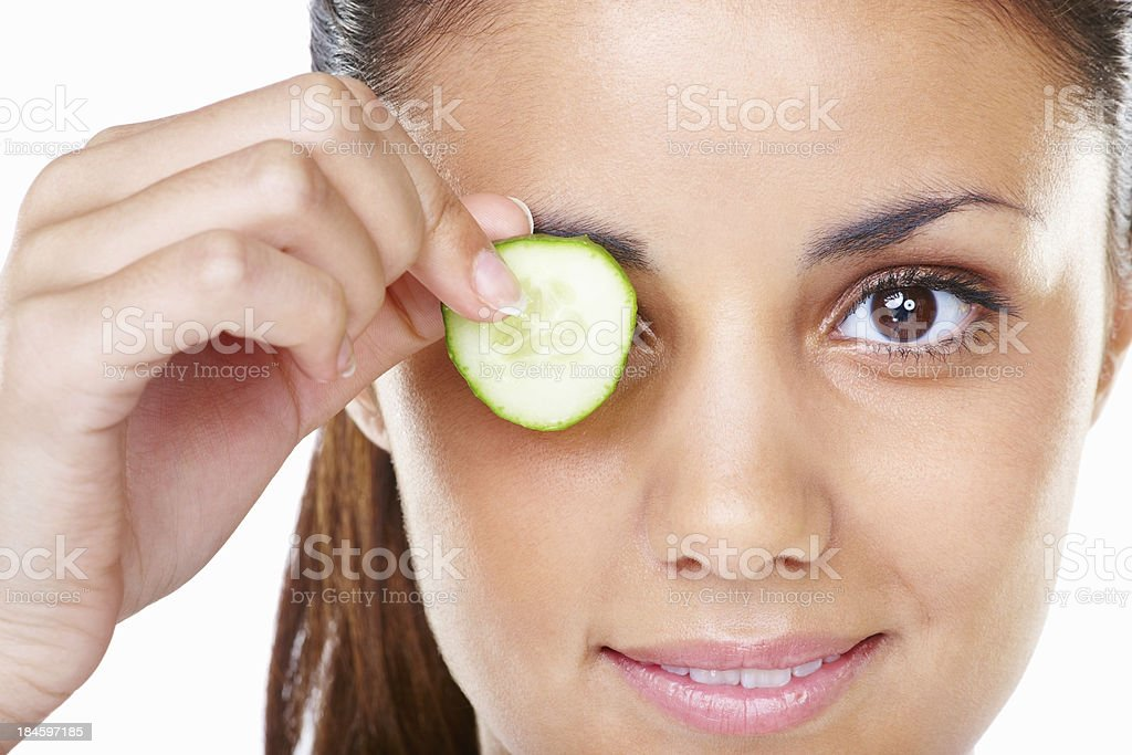 Beautiful young woman holding cucumber slice royalty-free stock photo