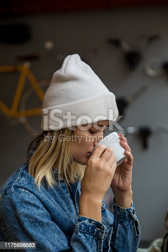 Young woman holding cup of coffee or tea in cafe.
