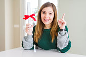 istock Beautiful young woman holding degree with red bow surprised with an idea or question pointing finger with happy face, number one 1134224409