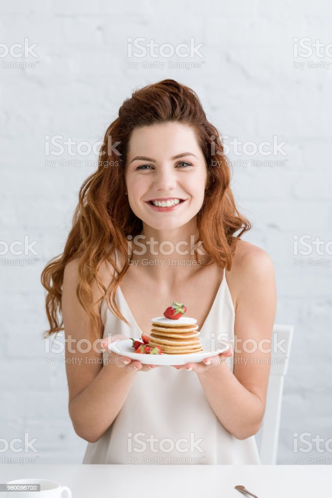 beautiful young woman holding delicious pancakes on plate and looking at camera stock photo