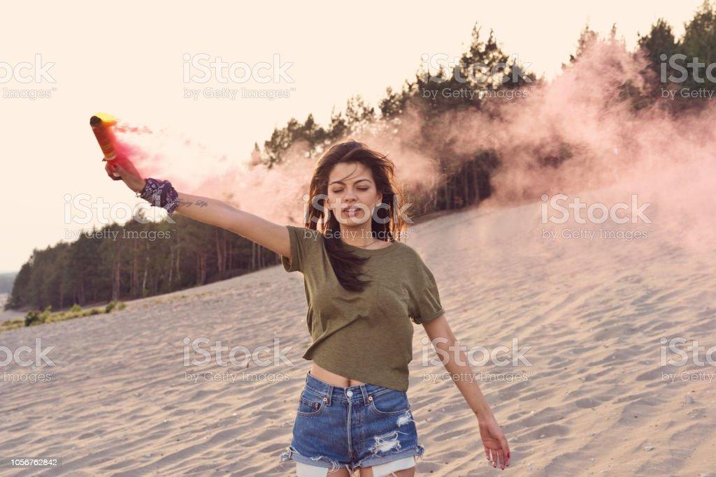 Beautiful young woman holding distress flare on the desert Beautiful young woman standing on the dune and holding distress flare in hand. 20-24 Years Stock Photo