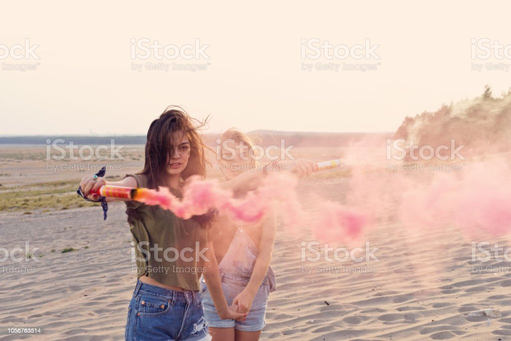 Beautiful young woman holding distress flare on the desert Two young women standing on the dune, brunette holding distress flare in hand. Adolescence Stock Photo
