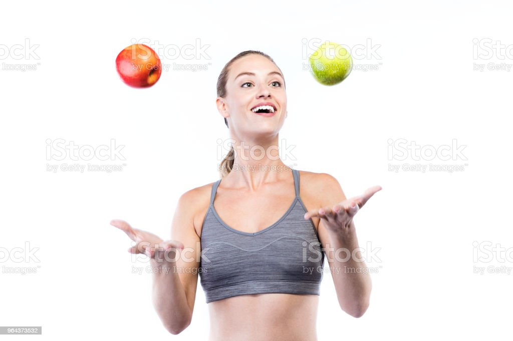 Mulher jovem e bonita segurando maçãs verdes e vermelhas sobre fundo branco. - Foto de stock de Adulto royalty-free