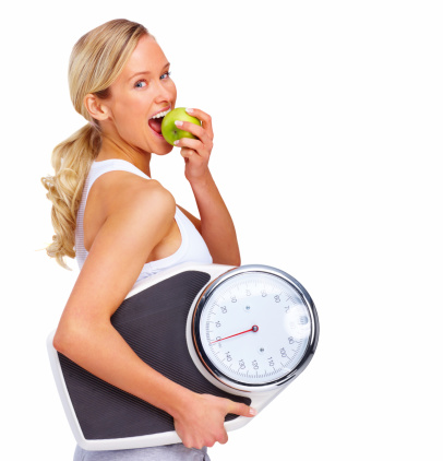 Beautiful young woman holding measuring instrument and eating an apple.