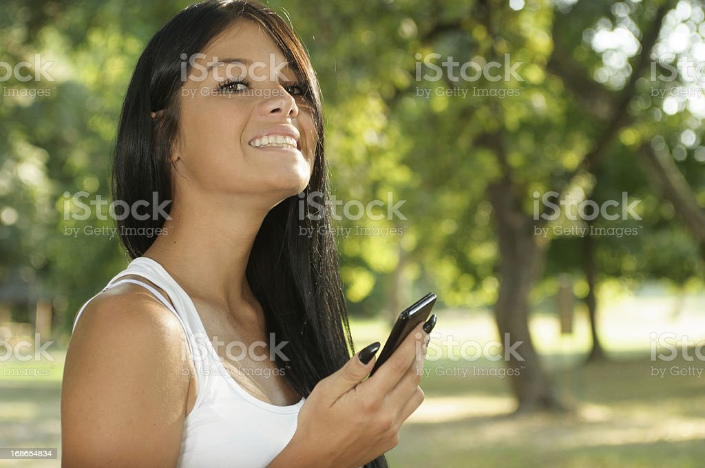 Beautiful young woman holding mobile phone royalty-free stock photo