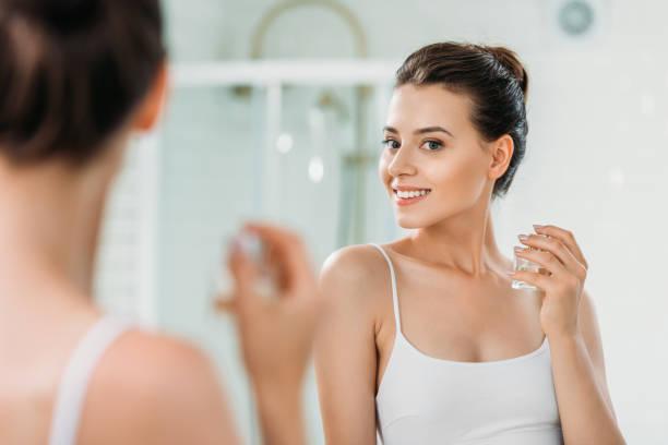 vacker ung kvinna håller parfymflaska och tittar på spegeln i badrummet - parfym bildbanksfoton och bilder