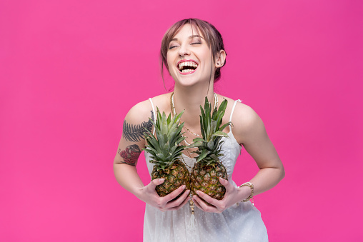 beautiful young woman holding pineapples and laughing isolated on pink
