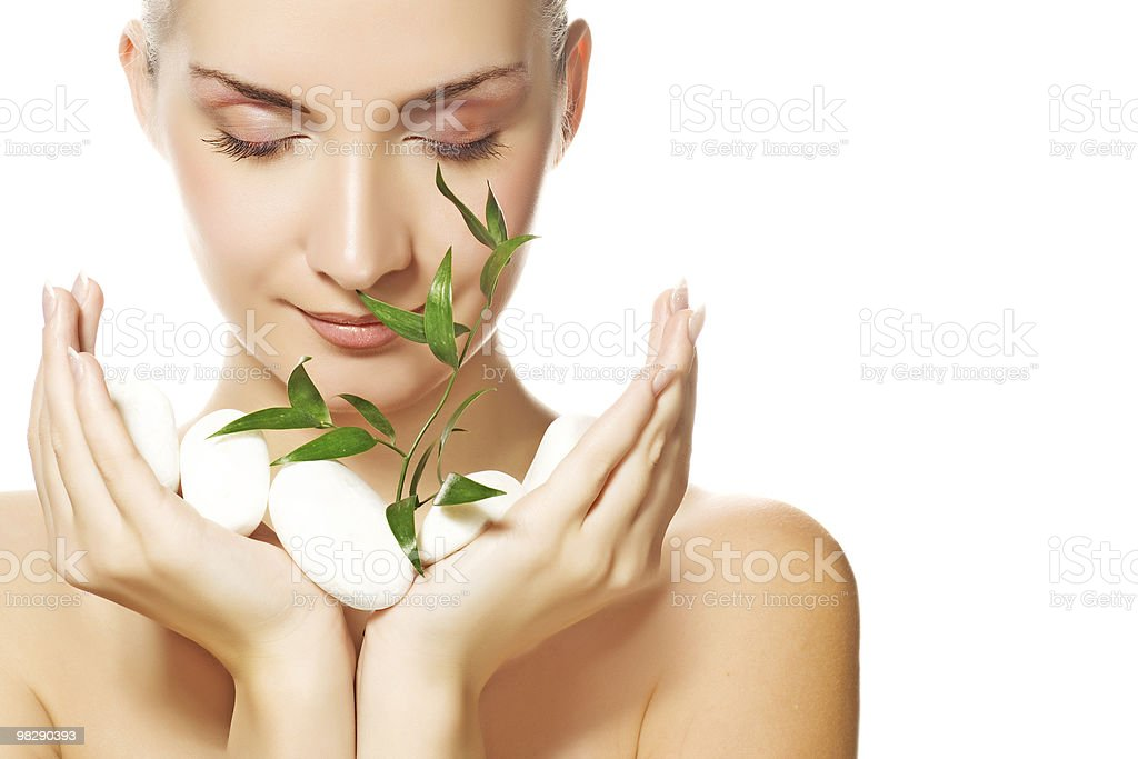 Beautiful young woman holding plant growing up through stones royalty-free stock photo