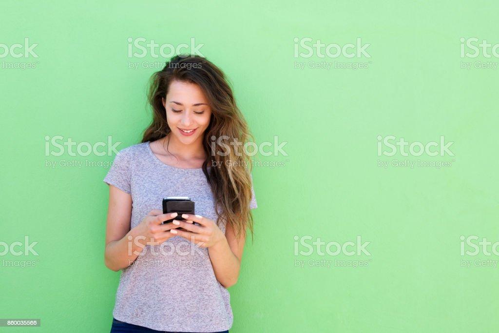 belle jeune femme tenant le téléphone intelligent sur fond vert - Photo