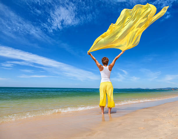 Beautiful young woman holding yellow fabric on wind stock photo