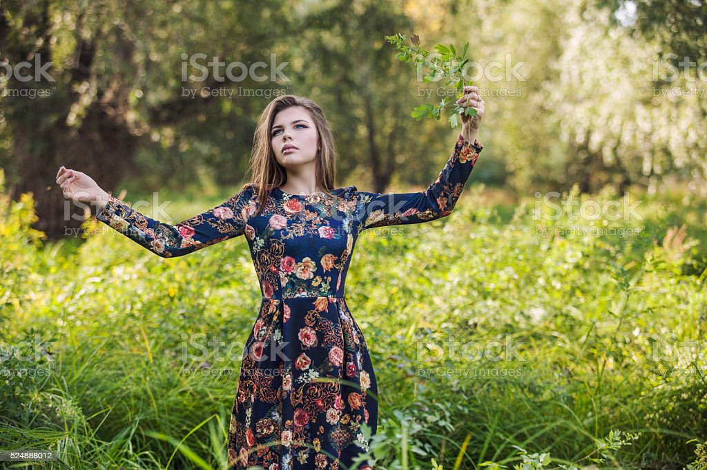 Beautiful young woman in a dress of nature stock photo
