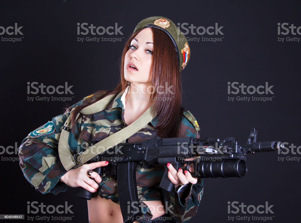 Beautiful young woman in a military uniform with an assault rifle stock photo