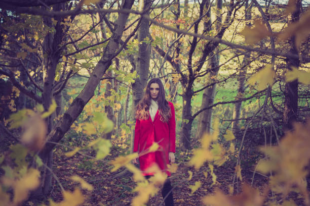 Beautiful, young woman in a striking red coat surrounded by autumnal yellow leaves stock photo