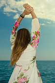 istock Beautiful young woman in a summer dress standing on a coast 1017338744