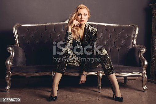 istock Beautiful young woman in a velours suit sits on a gray vintage couch 927780720