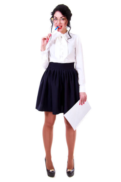 82d325ad31 Beautiful young woman in a white blouse and a black skirt licking a pen  stock photo