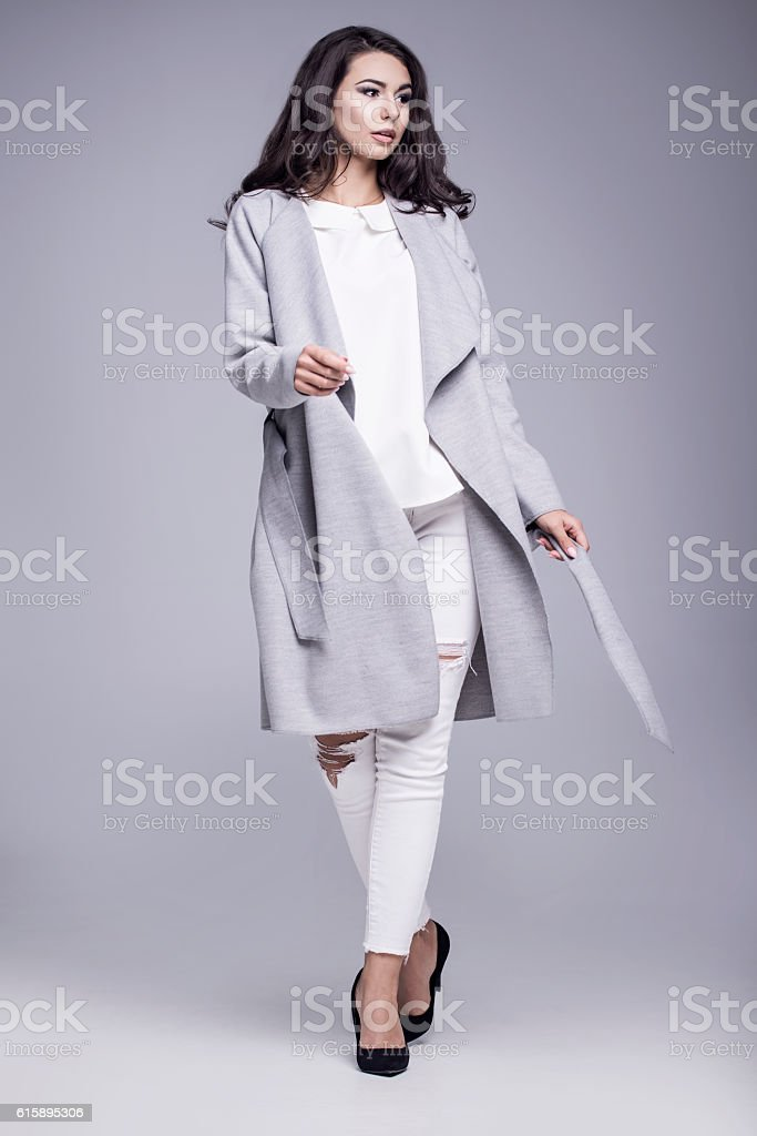 Beautiful young woman in an elegant gray coat stock photo