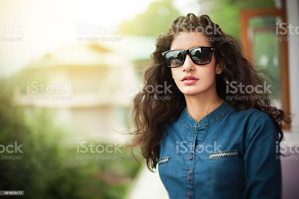 Beautiful young woman in balcony looking at view through sunglasses. stock photo