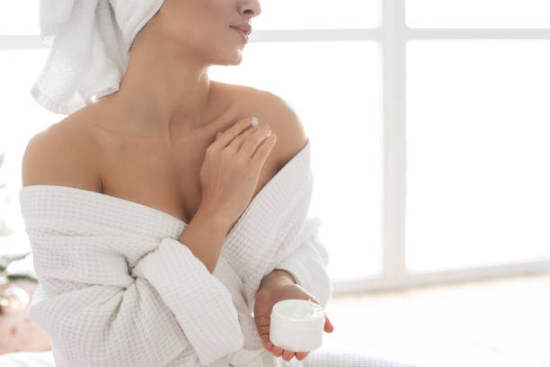 Beautiful young woman in bathrobe applying body lotion stock photo