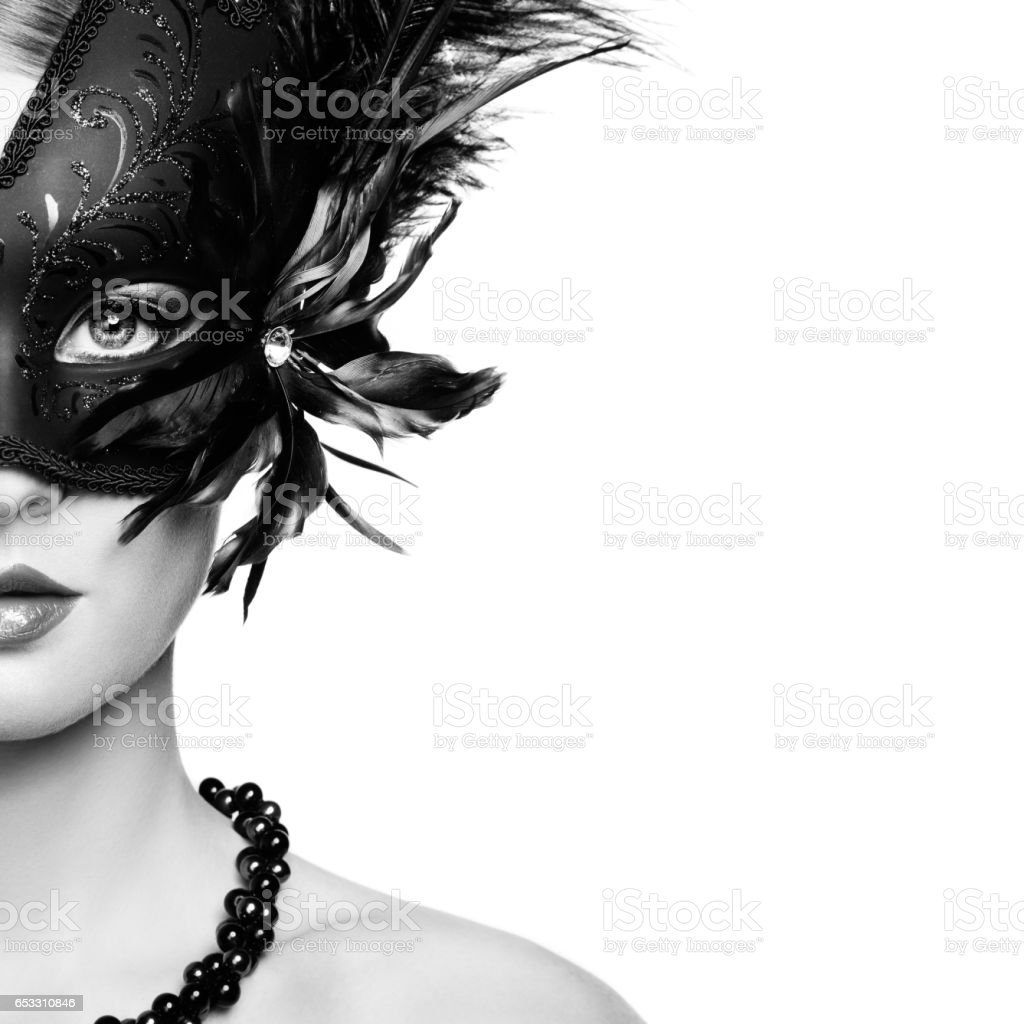 Beautiful young woman in black mysterious venetian mask stock photo