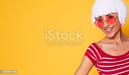 483075616 istock photo Beautiful young woman in blonde wig and pink sunglasses having fun on orange background, fashion blonde posing 1024947750