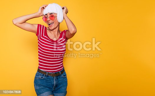 483075616 istock photo Beautiful young woman in blonde wig and pink sunglasses having fun on orange background 1024947808