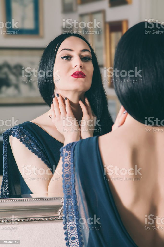 Beautiful young woman in blue dress with naked back stock photo