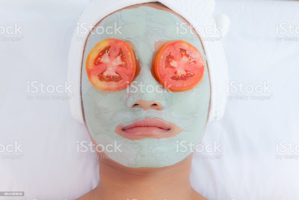 Schöne junge Frau in Ton-Schlamm-Maske auf Gesicht für Augen mit Scheiben Tomate Scheiben Gurke. – Foto