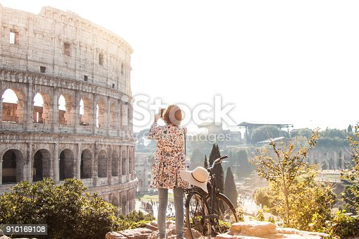 istock Beautiful young woman in colorful fashion dress alone on a hill with bike takes pictures of colosseum in Rome using smartphone camera at sunset. Attractive tourist girl with elegant straw hat 910169108