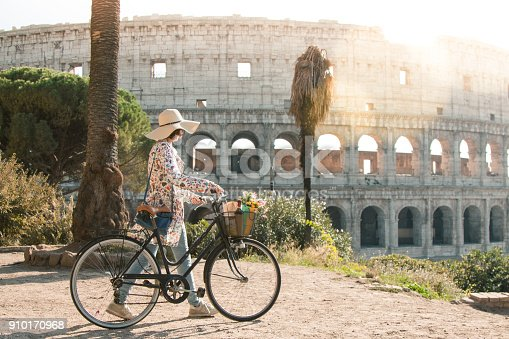 Beautiful young woman in colorful fashion dress walking alone on hill with her bike in front of colosseum in Rome at sunset with trees. Attractive tourist girl with straw hat. Lens Flare.