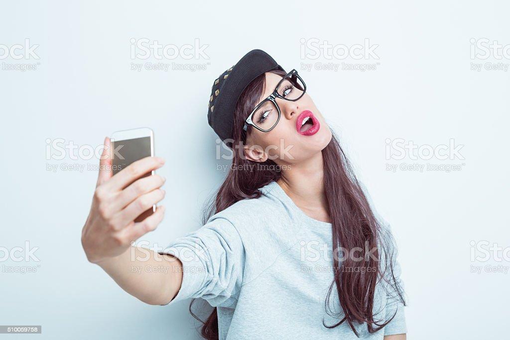Belle jeune femme en tenue contemporain prenant une autophoto - Photo de A la mode libre de droits
