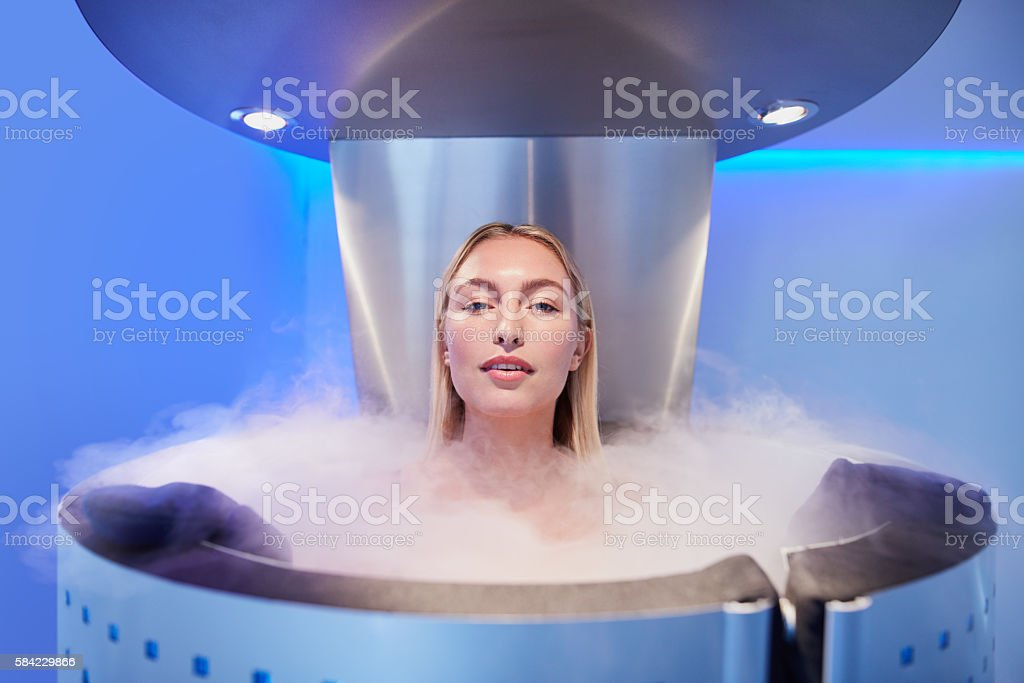 Beautiful young woman in cryosauna cabin Portrait of a beautiful young woman in cryosauna cabin for whole body cryotherapy. Caucasian female in freezing chamber with nitrogen vapors. Adult Stock Photo
