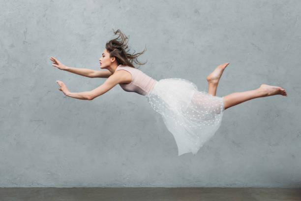 beautiful young woman in dress levitating and looking away on grey - on air stock photos and pictures
