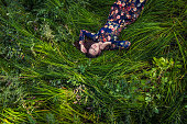 Beautiful young woman in dress lying in the grass