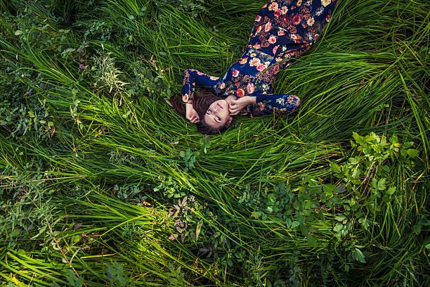 Bela jovem mulher no vestido deitado na grama - foto de acervo