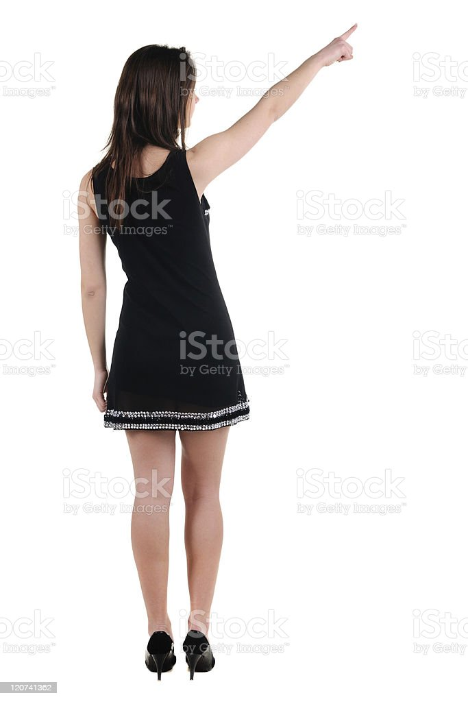Beautiful young woman in dress pointing at wall. Rear view. royalty-free stock photo