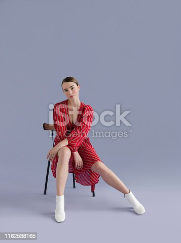 Young beautiful woman with brown hair put back in a stylish hairstyle wearing exclusive luxury designer clothing red striped dress looking confident fresh and lovely Fashion model studio portrait on purple background Ideal make-up and styling Sitting on the chair