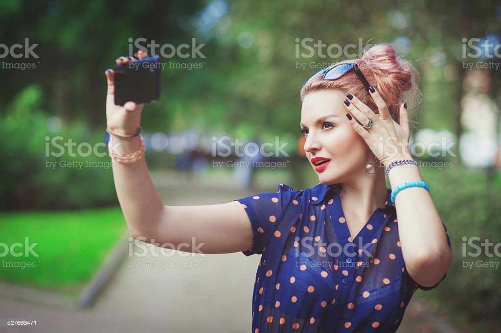 Beautiful young woman in fifties style taking picture of herself Beautiful young woman in fifties style taking picture of herself outdoor 1950-1959 Stock Photo