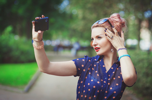 Beautiful Young Woman In Fifties Style Taking Picture Of Herself Stock Photo - Download Image Now