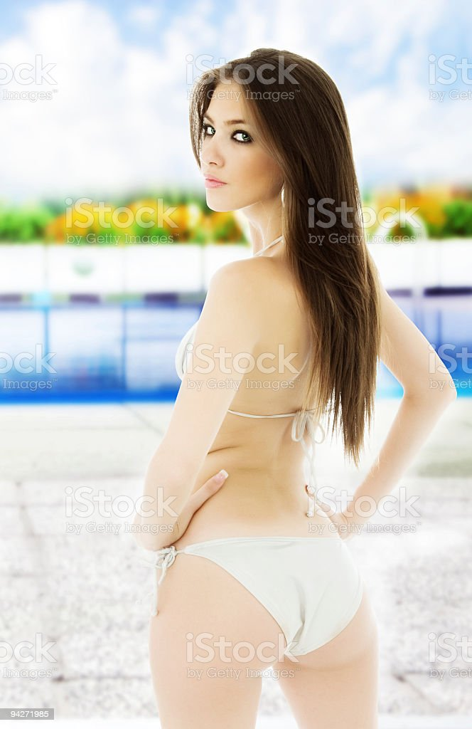 Beautiful young woman in front of the swimming pool royalty-free stock photo