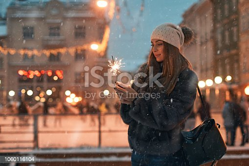 istock Beautiful young woman in fur coat holding a sparkler enjoys winter Christmas mood in old snowy European city with outdoor skating rink on background 1060116104