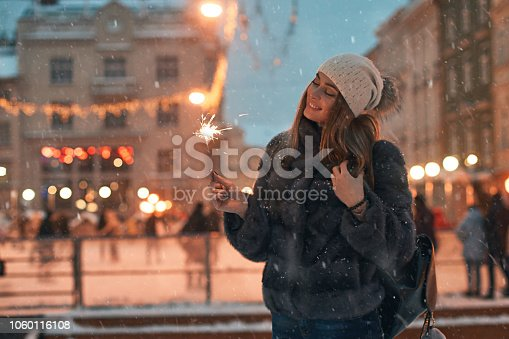 istock Beautiful young woman in fur coat holding a sparkler enjoys winter Christmas mood in old snowy European city with outdoor skating rink on background 1060116108