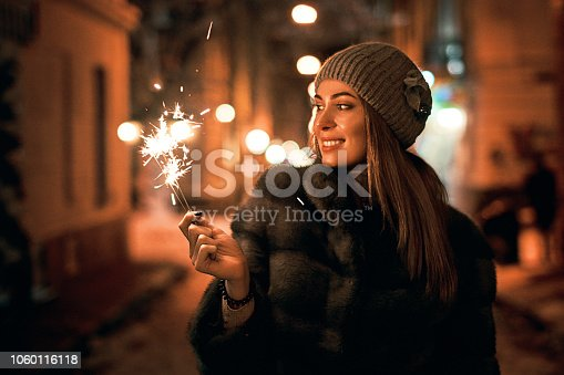 istock Beautiful young woman in fur coat holding a sparkler enjoys winter Christmas mood in old snowy European city on dark background 1060116118