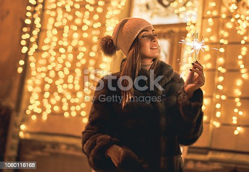 istock Beautiful young woman in fur coat holding a sparkler enjoys winter Christmas mood in old snowy European city on festive yellow lights bokeh background 1060116168
